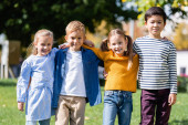 Multicultural kids smiling at camera while hugging in park