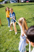 Cheerful kids plying tug of war with friends on blurred foreground in park