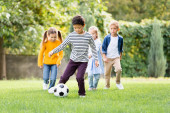 Asian boy playing football near friends on blurred background in park