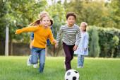 Vidám, többnemzetiségű gyerekek fociznak barátok közelében elmosódott háttérrel a parkban