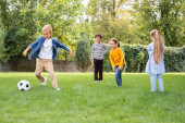 Positive multiethnic children standing near friend playing football in park