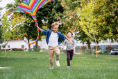 Cheerful boy running with flying kite while playing with asian friend in park