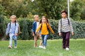 Multikulturní školáci procházky s batohy na trávníku v parku