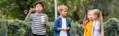 Asijské chlapec foukání mýdlo bubliny poblíž usmívající se přátelé venku, banner