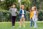 Asian boy blowing soap bubbles while standing near smiling friends on grassy lawn