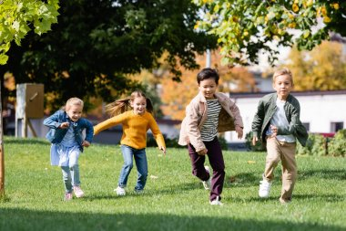 Smiling multiethnic children running on grass in park stock vector