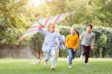 Girl holding flying kite while running near multiethnic friends in park stock vector