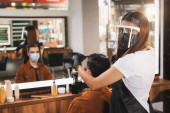 fodrász az arc pajzs vágás haj ügyfél orvosi maszk közelében elmosódott tükör visszaverődés
