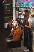 muž v lékařské masce dotýkající se jeho vlasů u kadeřnictví v obličejovém štítu držící hřeben a nůžky, rozmazané popředí