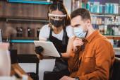 fodrász arcvédő és latex kesztyű digitális tabletta közelében ügyfél orvosi maszk, homályos előtér