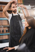young bearded barber in apron cutting hair of woman