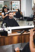 mirror reflection of young barber cutting hair of bearded man, blurred foreground
