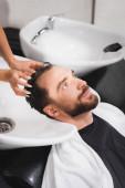 holič mytí vlasů mladého vousatého muže v salonu krásy