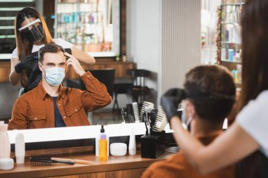 Mirror reflection of hairdresser in face shield cutting hair of man pointing with fingers, blurred foreground stock vector