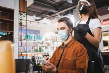 Hairdresser in protective equipment standing with comb behind client using smartphone, blurred foreground stock vector
