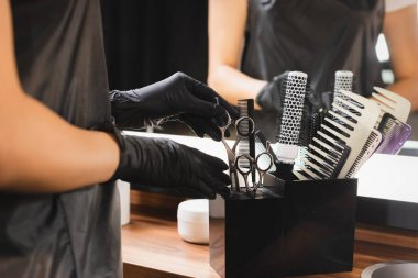 Partial view of hairdresser in latex gloves putting scissors in holder with combs on blurred background stock vector