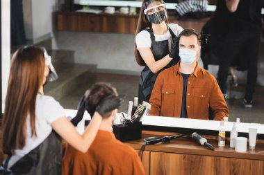 Mirror reflection of barber in face shield and latex gloves near client in medical mask on blurred foreground stock vector