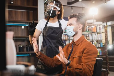 Hairdresser in protective equipment touching hair of man in medical mask showing refuse gesture stock vector