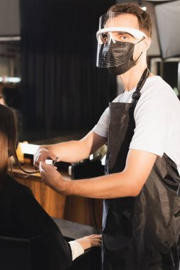Barber in face shield cutting hair of client while looking at camera stock vector