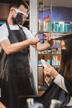 Hairdresser in protective equipment cutting hair of woman using smartphone, blurred background stock vector