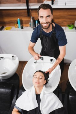Smiling, bearded hairdresser washing hair of young woman in barbershop stock vector