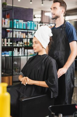 Bearded barber standing behind woman with hair wrapped in towel stock vector