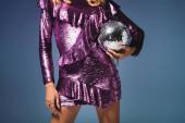 oříznutý pohled na elegantní žena v flitrové šaty s diskotéka míč na modrém pozadí