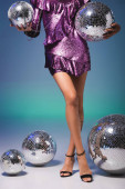 cropped view of elegant woman in sequin dress posing with disco balls on blue background