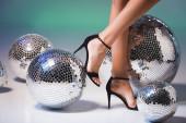 női lábak fekete cipőben és fényes diszkó labdák