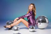 usmívající se elegantní žena v flitrové šaty pózující na podlaze s disco kuličkami