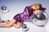 elegantní žena v flitrové šaty pózovat na podlaze s disco kuličkami