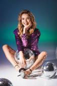 šťastná elegantní žena v flitrové šaty pózovat na podlaze s disco kuličkami