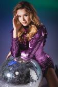 elegáns nő flitteres ruhában pózol disco ball