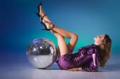 usmívající se elegantní žena v flitrové šaty ležící na podlaze s diskotékou