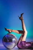 cropped view of elegant woman in sequin dress lying on floor with disco ball