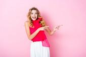 elegáns boldog nő korona mutatva félre rózsaszín háttér