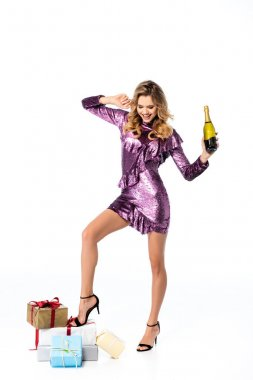 smiling elegant woman in sequin dress with champagne and gifts isolated on white