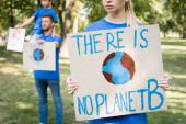 Frau hält Plakat mit Globus und es gibt keine Planet-b-Inschrift in Familiennähe mit Plakaten auf verschwommenem Hintergrund, Ökologiekonzept
