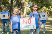 gyermekek gazdaság placard bolygó nélkül b felirat közelében szülők plakátok elmosódott háttér, ökológia koncepció