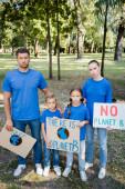 rodina dobrovolníků držících plakáty s globem a bez nápisu na planetě b, koncept ekologie