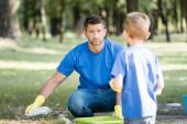 férfi gyűjtése műanyag szemét a parkban közelében fia elmosódott előtérben, ökológia koncepció