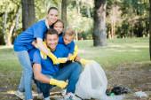 veselá rodina objímající otce držícího recyklovanou tašku v lese, koncept ekologie