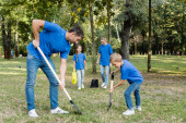 father and son digging ground while mother and daughter carrying young tree and watering can, ecology concept