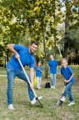 Photo father and son smiling at camera while digging ground, and mother with daughter holding young tree and watering can on blurred background, ecology concept