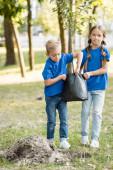 fiatal palántákat hordozó testvér és testvér a parkban, ökológiai fogalom