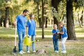 Kinder, die junge Sämlinge in der Nähe der Eltern mit Schaufel und Gießkanne tragen, ökologisches Konzept