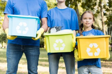 Family of activists holding containers with recycling symbols, full of plastic rubbish, ecology concept stock vector