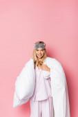 Fröhliche Frau in Pyjama und Augenbinde mit Decke auf rosa Hintergrund