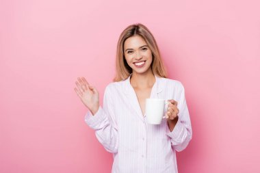 Smiling woman in pajamas holding cup and waving hand on pink background stock vector