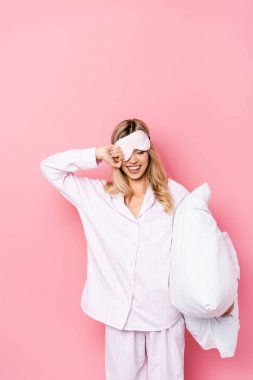 Cheerful woman in blindfold and pajamas holding pillow on pink background stock vector